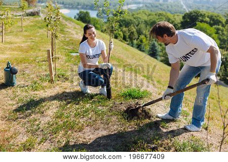 Adding their bit. Strong motivated handsome guy digging a hole with a shovel while his colleague holding a nursery plant while they both working as volunteers