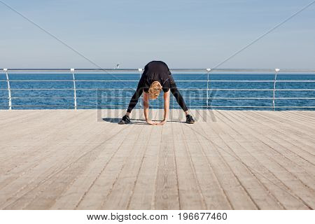 Man in sportswear warming up on wooden pier with sea on background.