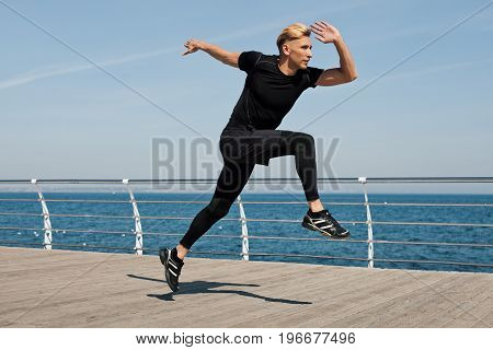 Young blonde man wearing black sporty outfit making leap on wooden pier.
