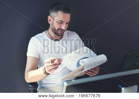 Getting information. Trendy bristled employee wearing casual clothes is sitting at his working place in office and reading documents while expressing interest