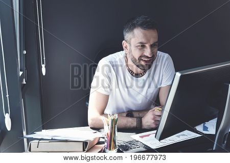 High spirits. Happy manager with stubble is sitting at table with rubber sphere in his hand and looking at screen of computer with smile. He is working with charts while expressing joy