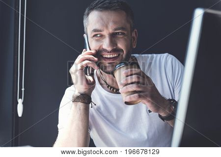 Informal conversation. Portrait of joyful bearded man is sitting with espresso in office while talking on smartphone and expressing gladness. He is looking aside with smile on grey wall background