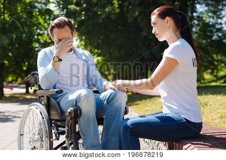 Traumatic experience. Passionate dedicated smart lady working with an injured man who sitting in a wheelchair and helping his recover