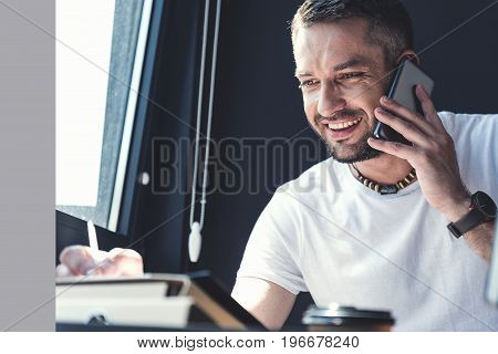 Signing major deal. Portrait of joyful stylish bristled manager is having pleasant communication on handset and expressing happiness while making notes in his notepad. Copy space in the left side
