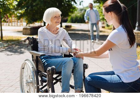 Quick recovery. Lively graceful aged lady sitting in a wheelchair and recovering from leg injury while young woman providing her with psychological support