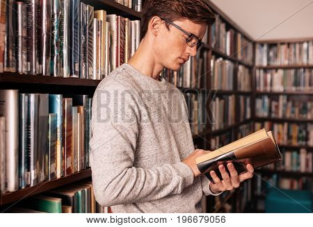 Young university student reading a book in library. College student standing by bookshelf in library with a book.