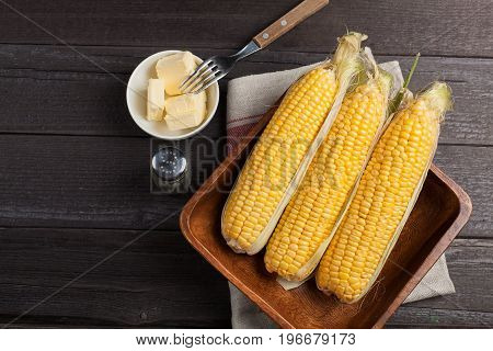 Fresh Corn On The Cob With Salt And Butter On Wooden Table, Closeup, Top View. Dark Background With