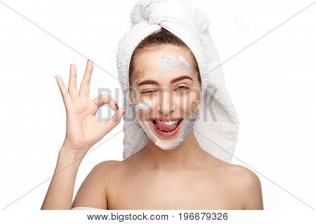 Young girl with cosmetics on face and towel on head showing OK gesture on white background.