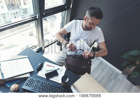 Time to go. Top view of modish bearded manager is sitting in chair while holding documents with bag and looking at his watch