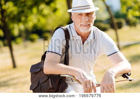 Let me think. Delighted grey-haired man leaning arms on handle bar and keeping smile on his face while looking aside