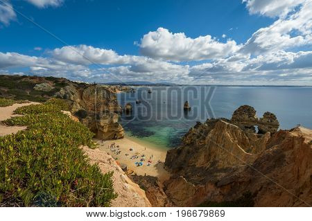 Praia do Camilo Portugal - July 6 2017: People at the beautiful Camilo Beach (Praia do Camilo) and the surrounding cliffs in Lagos Portugal