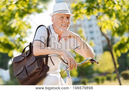Having rest. Positive delighted retirement keeping smile on his face and holding backpack on shoulder while putting elbows on handle bar