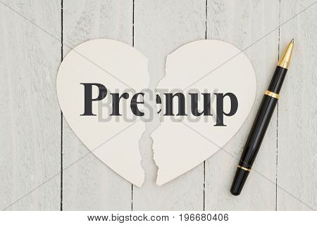 Writing up your prenuptial agreement Heart-shape card on weathered wood background with text Prenup on each piece of the card