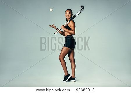 Happy Young Woman Holding Hockey Stick And Ball