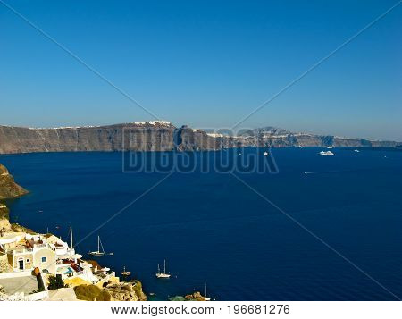 Santorini volcano caldera lit by afternoon sunshine, view from Oia, Santorini island, Cyclades, Greece