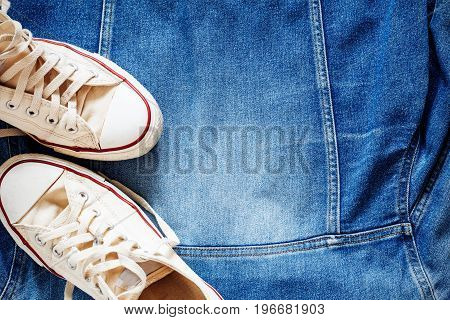 Old sneakers on a blue denim jacket.