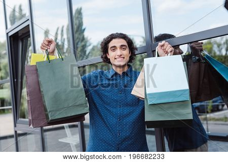 Cheerful Handsome Young Man Holding Shopping Bags And Smiling At Camera