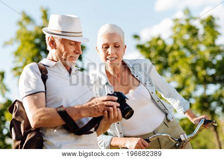 Let me see it. Delighted blonde keeping smile on her face and looking downwards while sitting on the bicycle