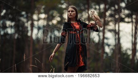 Girl in red and black dress stands with owl on her hand in forest and looks away.