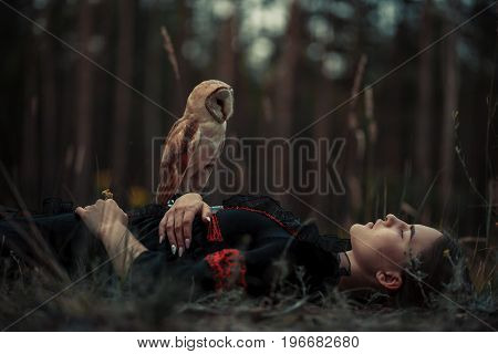 Girl in red and black dress lies with owl on grass in forest. Owl sits on her hand.