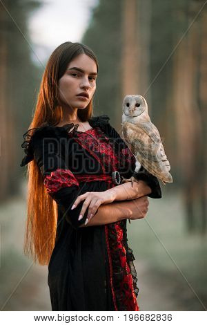 Portrait of girl with long hair in red and black dress in forest with owl. Owl sits on her hand. Close-up.