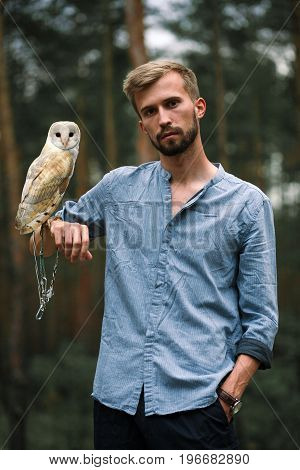 Portrait of young man in blue shirt with owl in forest. Owl sits on his hand and is tied to his arm by chain.