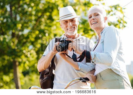 Happy couple. Pretty female person standing in semi position near her man while keeping smile on face and holding professional camera