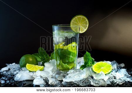 Mojito, a cool cocktail of lime and mint and soda, in a highball glass with ice, on a dark background