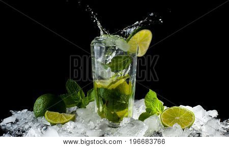 Mojito, a cool cocktail of lime and mint and soda, in a highball glass with a splash and ice, isolated on a black background