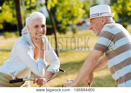 Feeling young. Attentive husband feeling happiness while looking at his wife and leaning on handle bar