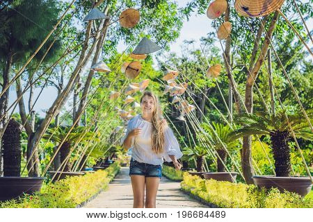 Young woman tourist and Vietnamese hats. Travel around Vietnam concept.