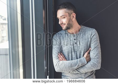 Passers-by outside. Stylish manager is looking through window with interest while standing with crossed arms and expressing curiousness. Copy space in the left side
