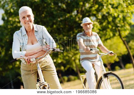 We are happy. Delighted blonde keeping smile on her face and holding hands together on the handle bar while enjoying weekends