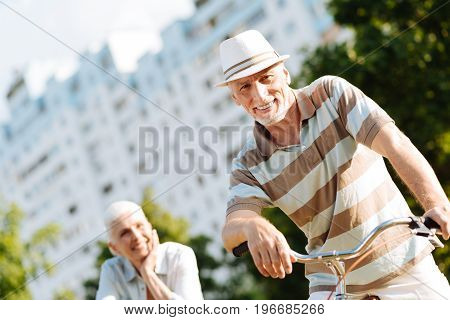 Invite you. Positive mature male person keeping smile on his face and putting hands on handle bar while sitting on the bicycle