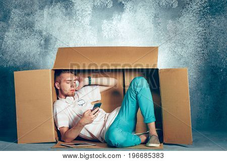Introvert concept. Man sitting inside box and working with phone