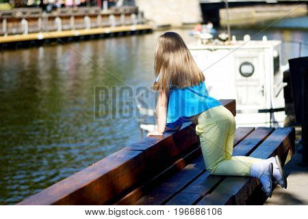 Adorable Little Girl Playing By A River In Sunny Park On A Beautiful Summer Day