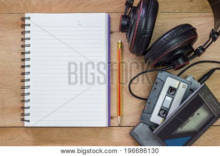 Bank notebook with pencil laying on the brown table. Vintage old tape player with headphones put on the table as well.