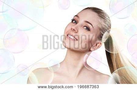 Beautiful sensual woman in soap bubbles isolated on white. Cleansing concept.
