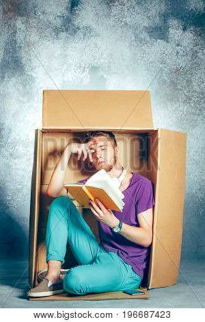 Introvert concept. Man sitting inside box and reading a book