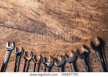 Top view of group of wrench arrange on wooden rustic background. flat lay with copy space for mechanic tools concept.