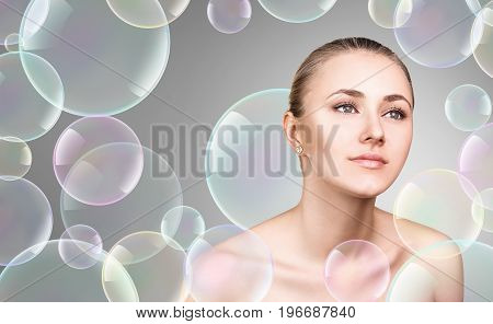 Beautiful sensual woman in soap bubbles over gray background. Cleansing concept.