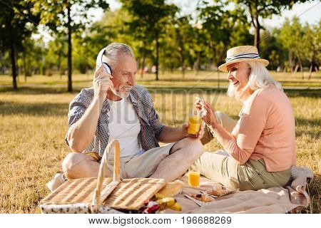 Favorite melody. Charming woman holding telephone in both hands and keeping smile on her face while sitting in semi position near her man