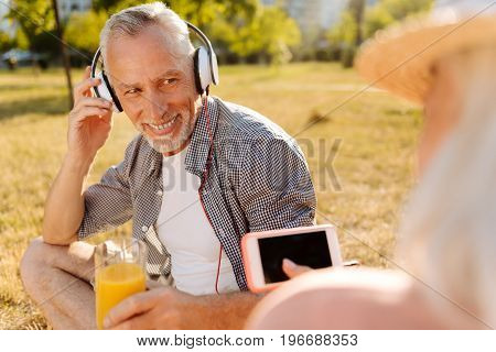 I am music lover. Attractive grey-haired male person holding glass with orange juice and touching headphones while leaning elbow on knee