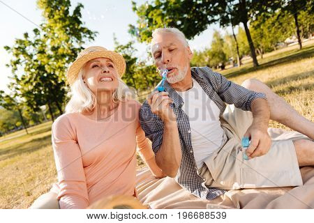 Make bubbles. Delighted bearded grey-haired male person looking downwards while blowing on special stick with soap and sitting on plaid near his wife