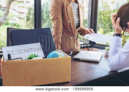 Close up of the hand employer filing final remuneration to resignation employee Man has stressed packing up all his personal belongings and files into a brown cardboard box resign concept.