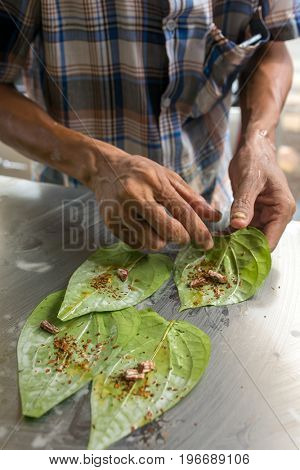 Man making betel nut on the street stall in Myanmar (Burma).