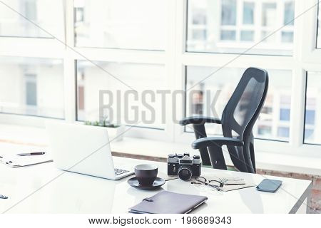 Modern office. Empty workplace with white laptop camera, coffee cup and other items. Big window with cityscape on background