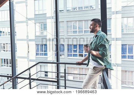 Feeling good. Profile of attractive man wearing casual clothes is leaning on railing and looking aside with smile while drinking coffee. Copy space in the left side