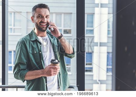 Staying in touch. Portrait of positive man in casual clothes is standing with coffee and talking on mobile phone. He is looking at camera with joy on big window background. Copy space in right side