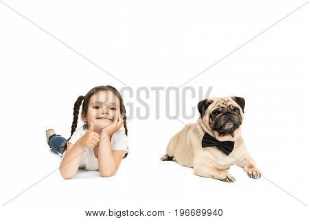 Little Adorable Girl Showing Thumb Up While Lying With Pug Dog In Bow Tie, Isolated On White